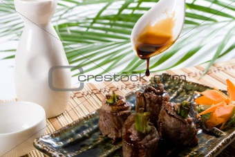 pouring soy sauce on beef roll
