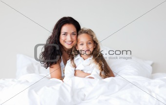Mother and daughter on bed smiling at camera