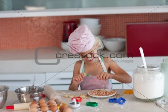Blond little girl baking in the kitchen