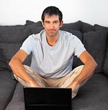 Man using laptop looking at camera