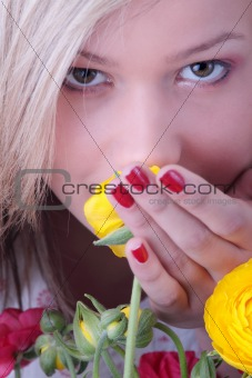 Blond woman hiding behind colorfoul flowers