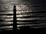 Lighthouse Silhouetted Against Ocean at Dusk