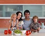 Young family smiling at camera indoors