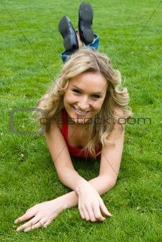 Blonde girl lying in the park