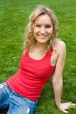 Blonde girl sitting on grass in a park