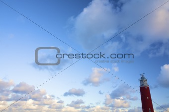 a classic red lighthouse against a blue sky in summer with white clouds