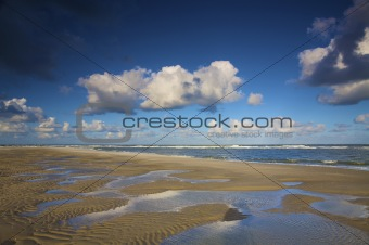 a beach at the sea in Holland in summer with a blue sky