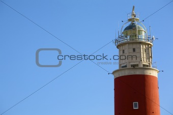 a classic red lighthouse against a clear blue sky in summer