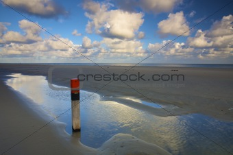 an empty beach at the sea in summer with a blue sky and white clouds