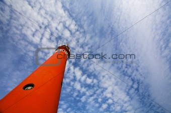 a red lighthouse against a cloudy blue sky in summertime