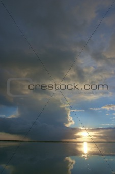 a thunder storm with dark rain clouds in summer over the ocean with a beautiful reflection and a blue sky