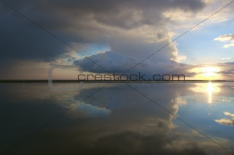 a thunder storm with dark rain clouds over the ocean with a beautiful reflection and a blue sky