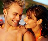 Smiling romantic young couple at the beach