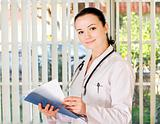 Portrait of female doctor standing in the office and holding med