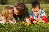 Woman and kids relaxing on the spring meadow