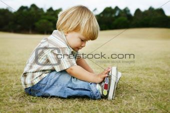 A thoughtful little boy sitting on the grass in a park.