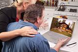 Couple In Kitchen Using Laptop with Lake Cabin on the Screen.