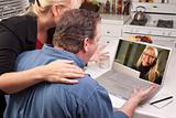 Couple In Kitchen Using Laptop with Customer Support Woman on the Screen.