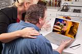 Couple In Kitchen Using Laptop with Singing Woman on the Screen.