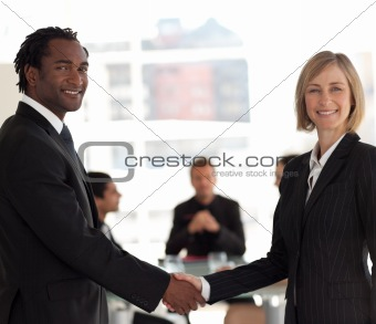 Business handshake in front of workgroup