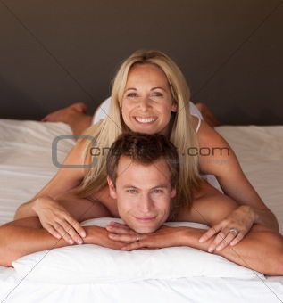 Beautiful woman on a mans back in bed