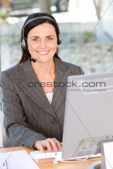 Portrait of woman wearing headset using computer