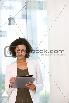 Portrait of business woman writing on notepad