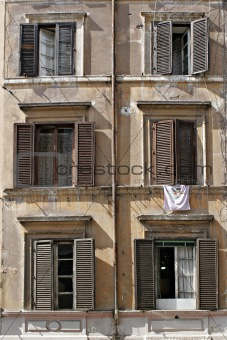 six windows with laundry and shutters in rome