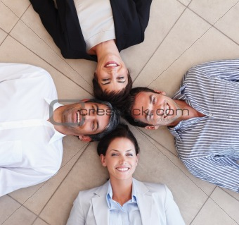 Happy business colleagues lying on the floor