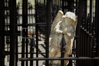 Angel behind wrought iron bars
