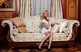 Flirting maid sitting on a sofa in luxury hotel