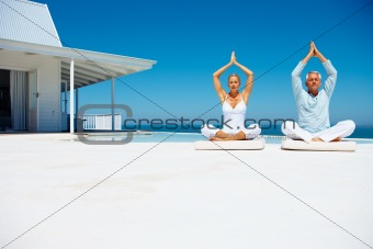 Attractive happy couple on the beach practicing yoga with a cottage in the background