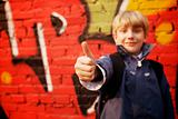 Kid standing in front of a graffiti wall