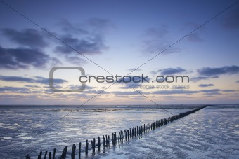 a colorful sunset at the beach with a blue sky