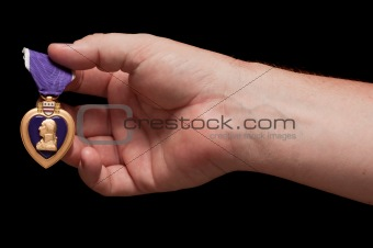 Man Holding Purple Heart War Medal on a Black Background.