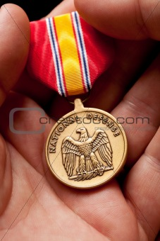 Man Holding National Defense War Medal in The Palm of His Hand.