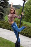beautiful girl dancing on the street lamp in the park