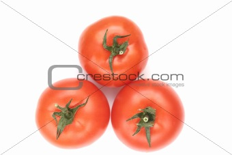 Three red tomatoes lay on a white background