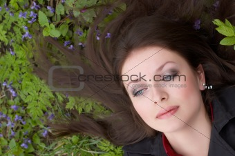 Beautiful brunette with blue eyes laying on the ground in the forest
