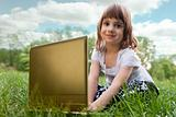Child with laptop sitting on a meadow