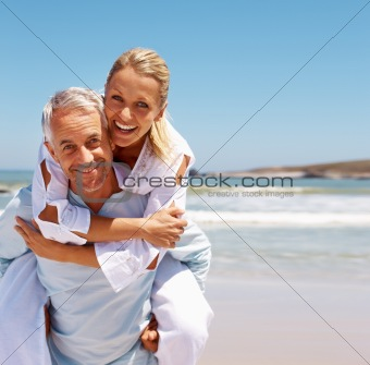 Husband carrying his wife on his back by the sea