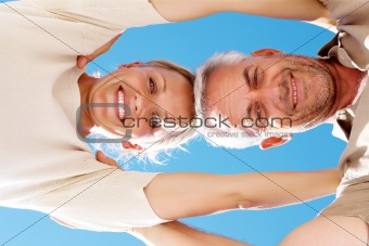 Smiling aged couple with blue sky in the background