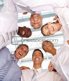 Upward view of smiling group of business executives in a huddle formation