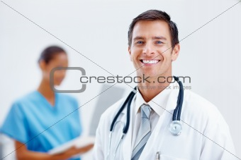 Happy and cheerful young doctor with a nurse at the background