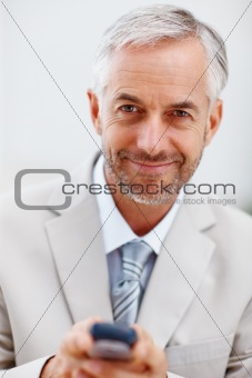 Mature business man using cellphone to text message