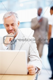 Senior business man working on a laptop with colleagues at the back
