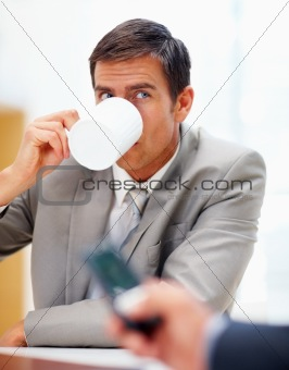 Business man drinking coffee while sitting in the office