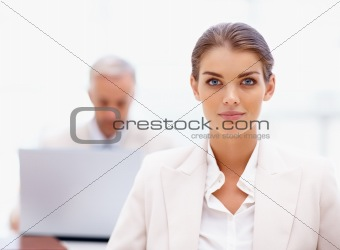 Closeup of attractive business woman with colleague in background