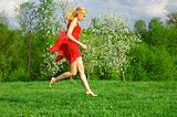 Young beautiful woman in a red dress jumping on lawn