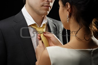 Business woman ties a necktie to a businessman